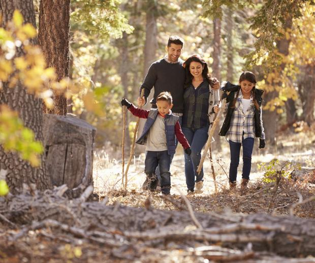 A family enjoys a fall hike. Photo credit: Adobe Stock