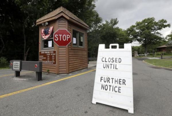 A sign sits at the entrance of Cheesequake State Park, which was closed amid the New Jersey government shut down. Photo credit: Julio Cortez